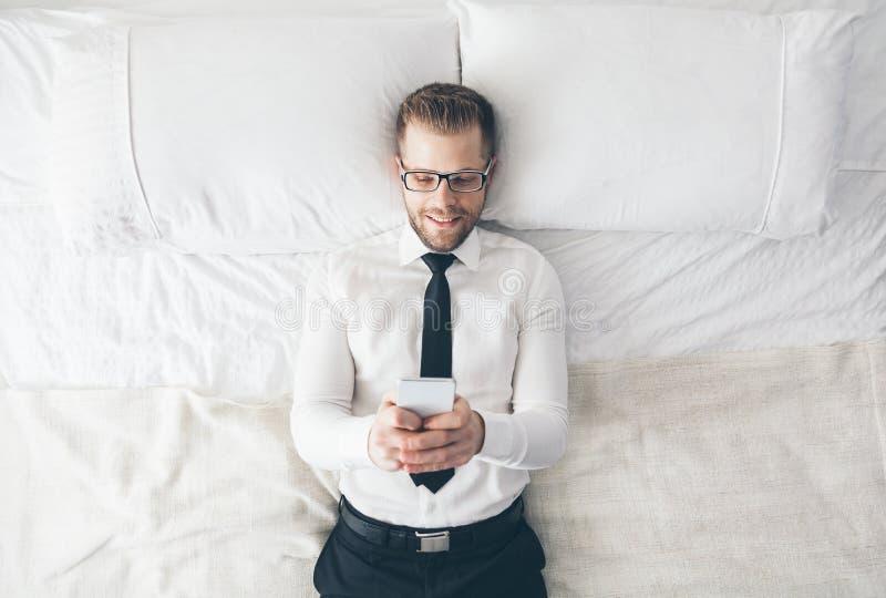 Vista superiore Uomo d'affari bello con i vetri che si trovano sul letto che manda un sms dal suo smartphone immagine stock