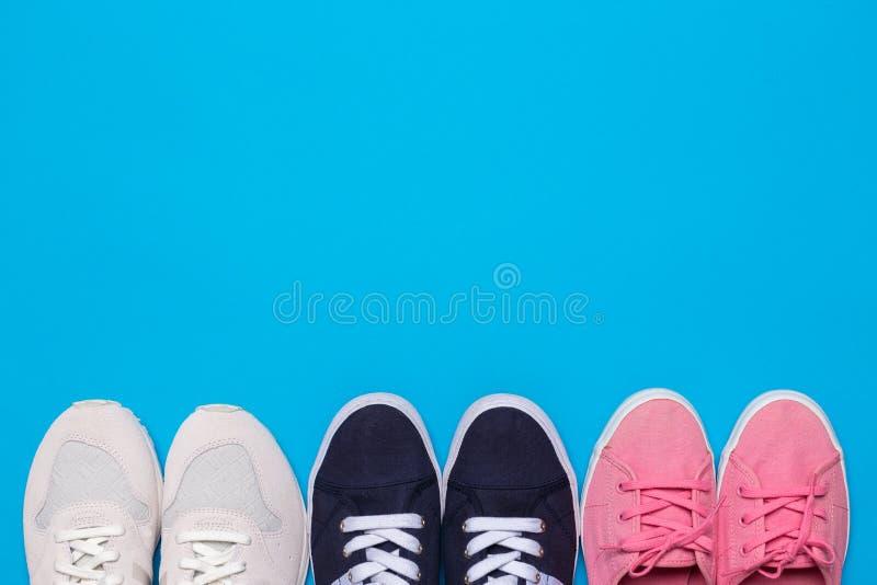 Vista superiore variopinta delle scarpe Metta delle scarpe da tennis differenti su fondo blu, spazio della copia fotografie stock