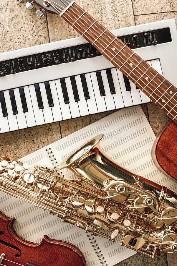 Vista superiore verticale degli strumenti musicali differenti: sintetizzatore, chitarra, sassofono e violino trovantesi sugli str immagine stock