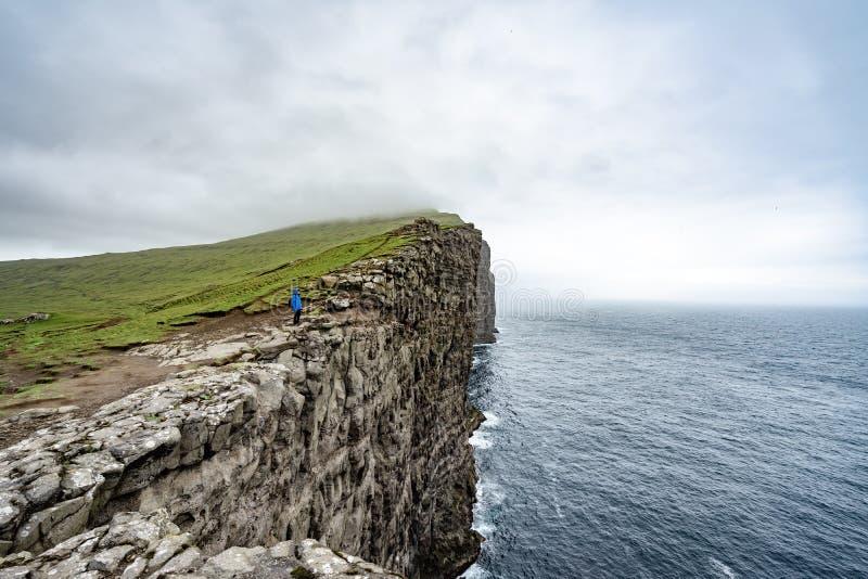 Vista surpreendente de montanhas do escravo do penhasco íngreme de Tralanipan na ilha de Vagar, Ilhas Faroé, Dinamarca Oceano Atl foto de stock