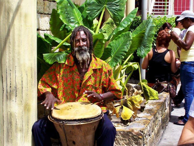 Vista típica en Antigua, músico de la calle con una señora que hace los panes imagenes de archivo