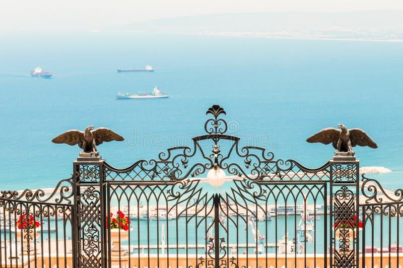 Vista tramite i portoni ai giardini di Bahai sul mar Mediterraneo Ciò è un'la più alta entrata ai giardini fatti di ferro forgiat immagini stock