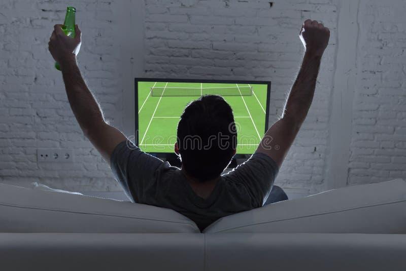 Vista traseira com fósforo de observação sozinho do tênis do grand slam da casa do homem novo na televisão no sofá imagens de stock