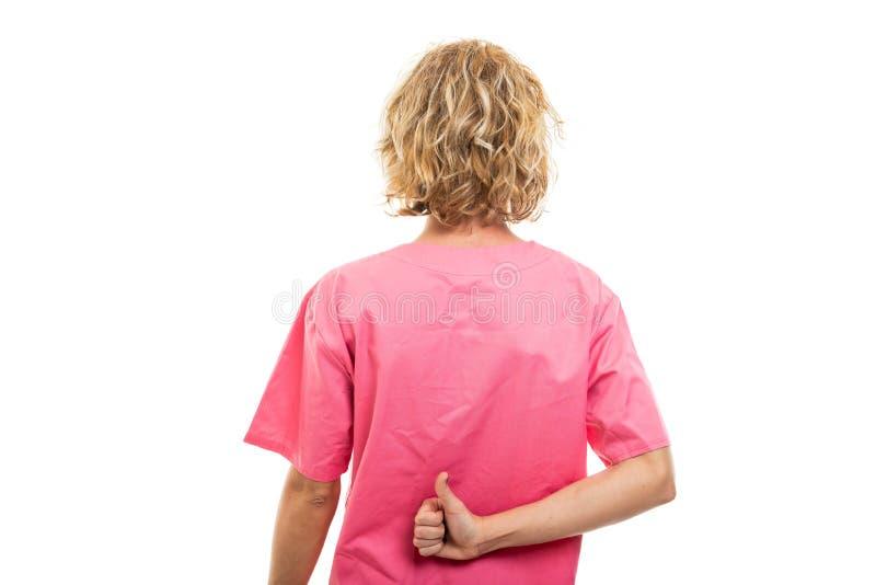 Vista traseira da enfermeira usando uma esfregona rosa mostrando como gesto imagem de stock