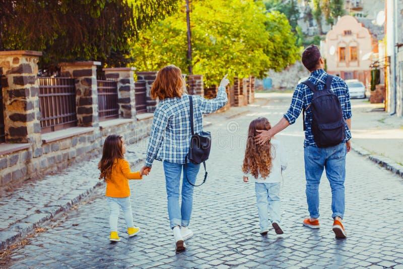 Vista traseira da família de quatro pessoas que anda a rua fotografia de stock royalty free