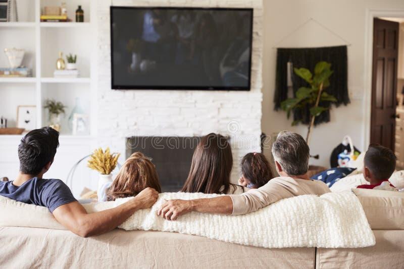 Vista traseira da família latino-americano de três gerações que senta-se no sofá que olha a tevê imagem de stock