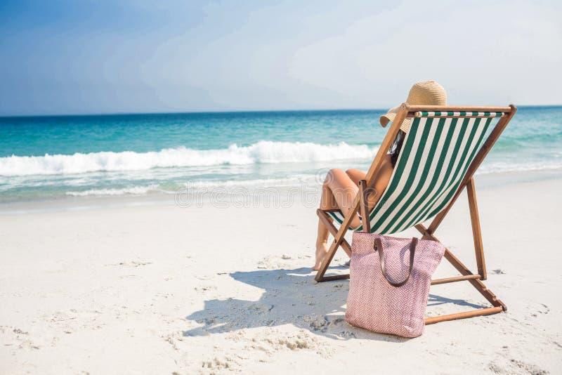 Vista traseira da morena bonita que relaxa na cadeira de plataforma na praia imagem de stock