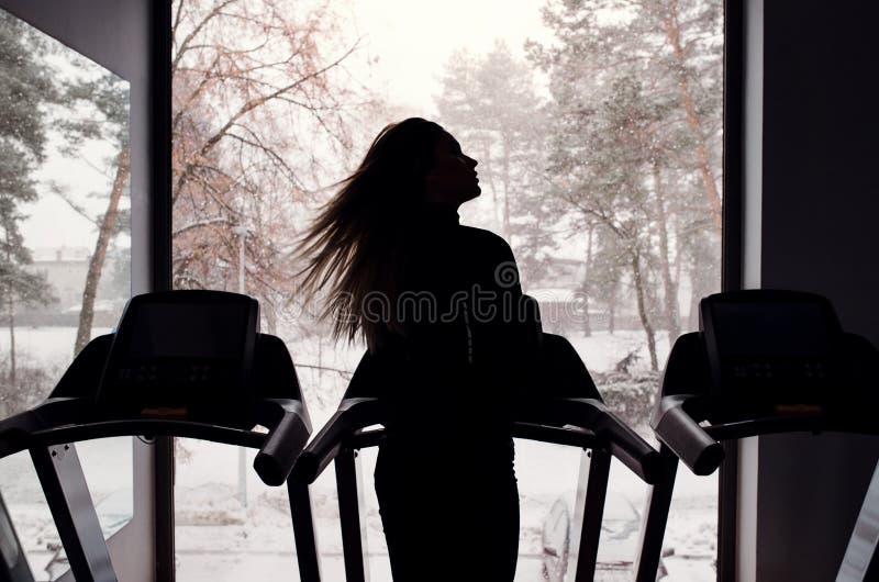 Vista traseira da silhueta da moça ou da mulher que fazem o cardio- exercício em um gym imagens de stock
