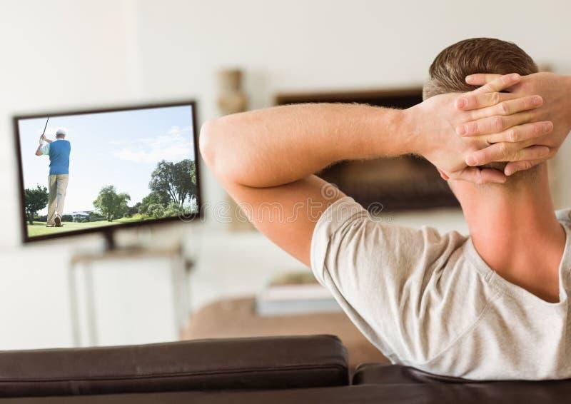 Vista traseira da televisão de observação do homem na sala de visitas imagens de stock royalty free