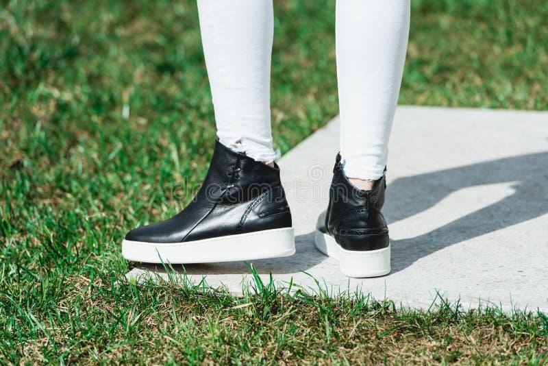 Vista traseira de botas de couro pretas do tornozelo da mulher Tiro exterior sobre a pedra branca no parque fotografia de stock royalty free