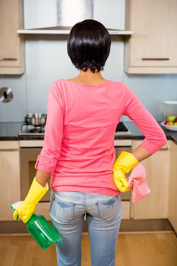A vista traseira de moreno ereto apronta-se para limpar a cozinha imagem de stock royalty free