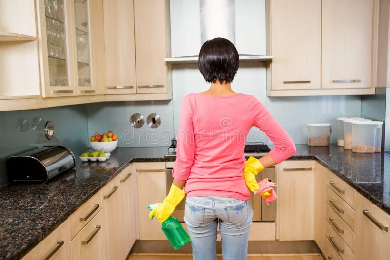 A vista traseira de moreno ereto apronta-se para limpar a cozinha imagem de stock