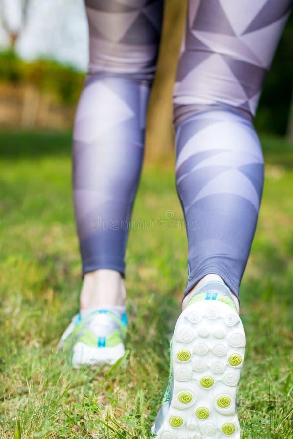 Vista traseira de sapatas running do esporte da mulher ativa imagem de stock
