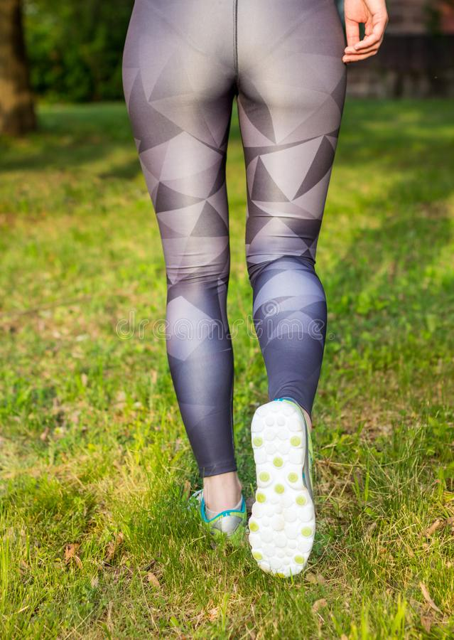 Vista traseira de sapatas running do esporte da mulher ativa fotografia de stock