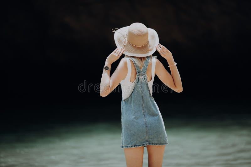 Vista traseira de um chapéu vestindo da mulher que aprecia a vista no oceano foto de stock royalty free