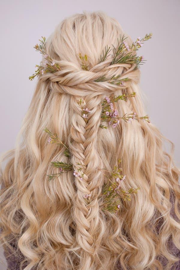 Vista traseira de um penteado na moda elegante, de umas ondas de entrelaçamento e de uma decoração com pétalas da flor fotos de stock