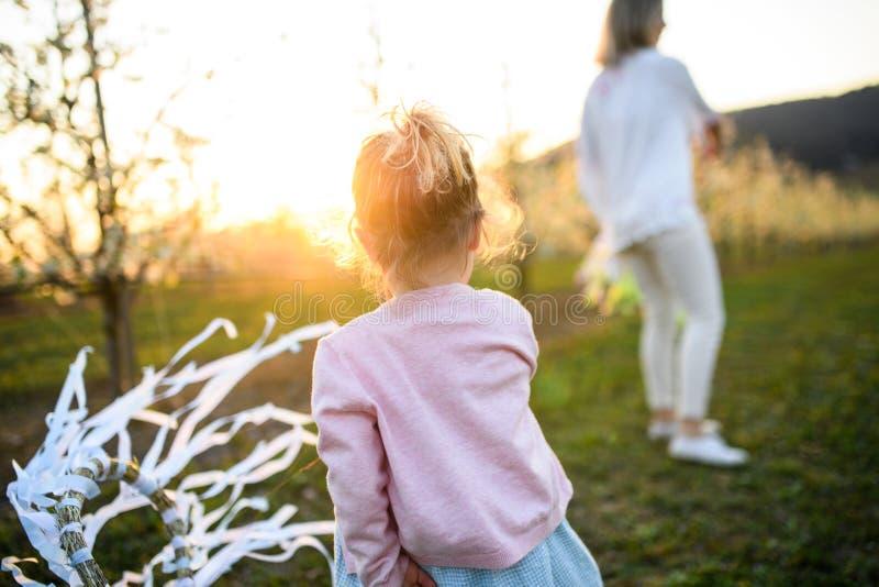 Vista traseira de uma menina pequena com mãe brincando ao ar livre na natureza da primavera ao pôr do sol imagem de stock