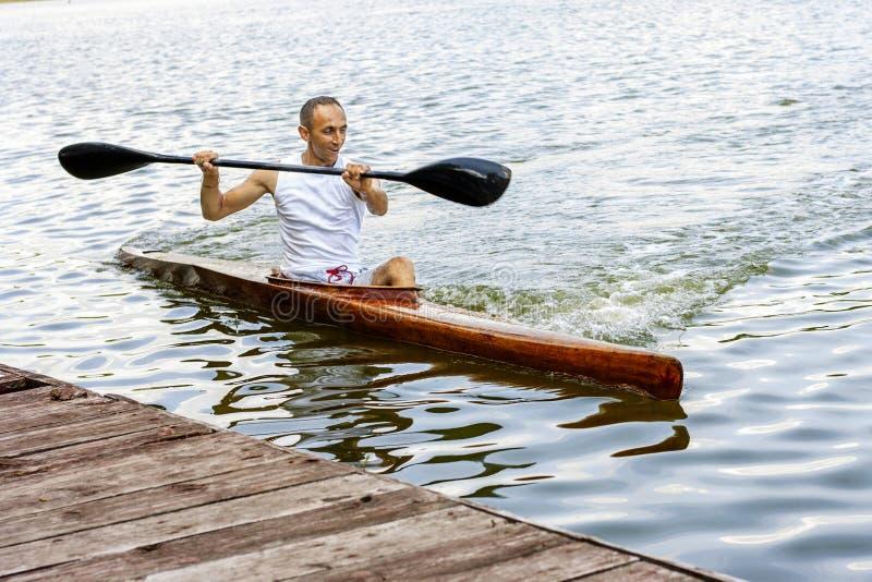 Vista traseira de uma pá do homem do kayaker uma canoa em um canal imagem de stock