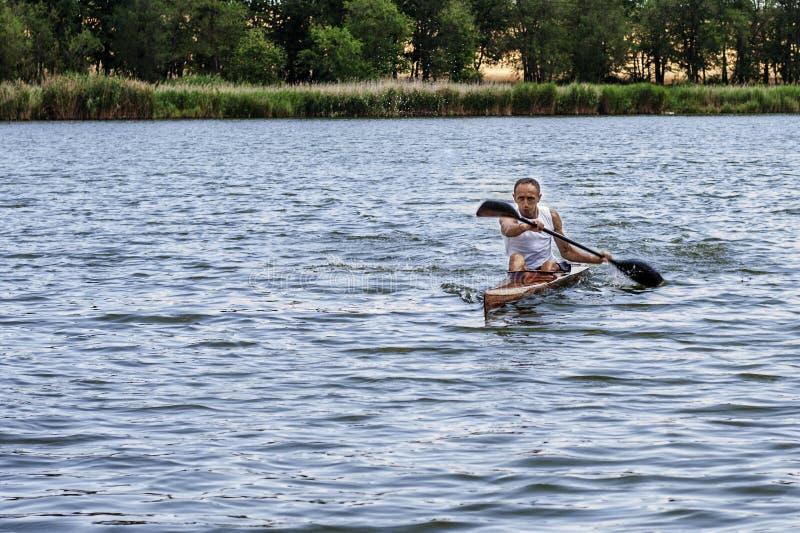 Vista traseira de uma pá do homem do kayaker uma canoa em um canal foto de stock royalty free