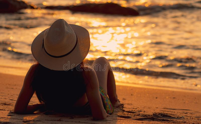 Vista traseira do biquini asi?tico do desgaste de mulher e do chap?u de palha que encontram-se para baixo na praia da areia para  foto de stock royalty free