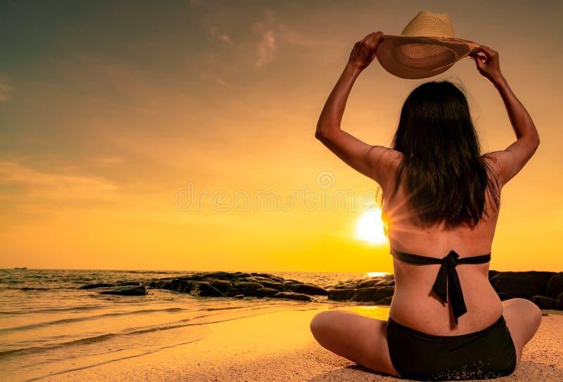 A vista traseira do biquini gordo asiático do desgaste de mulher e a mão que guarda o chapéu de palha sentam-se na praia da areia imagem de stock royalty free