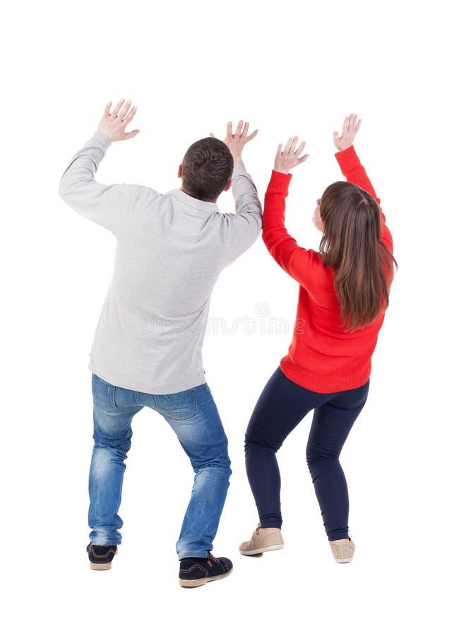 A vista traseira dos jovens que abraçam pares (homem e mulher) Ducked o prote imagens de stock
