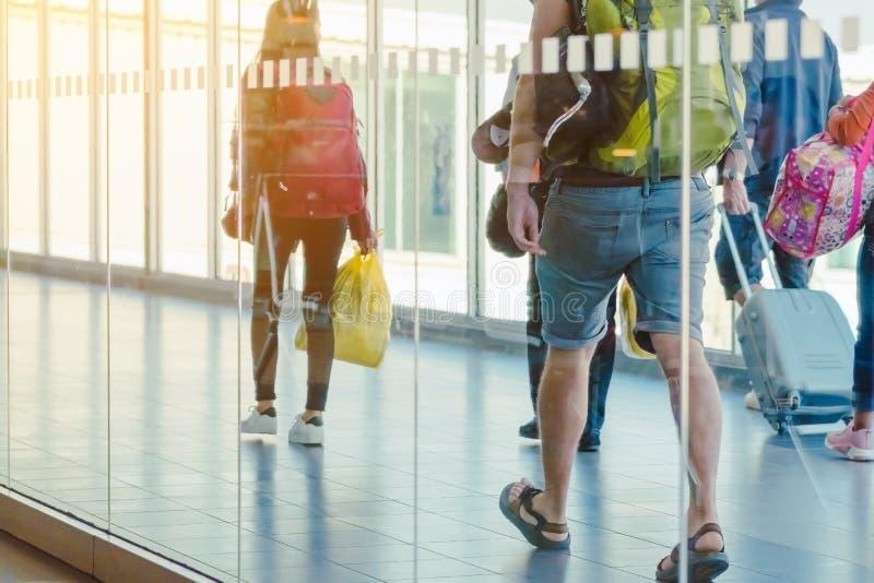 Vista traseira dos passageiros e da bagagem de viagem que andam o corredor do embarque do avião fotografia de stock