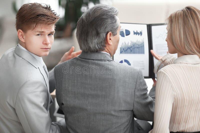 Vista traseira a equipe do negócio verifica o balanço financeiro imagens de stock royalty free