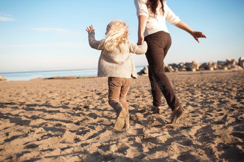 VISTA TRASEIRA: A filha pequena corre com sua mãe em uma praia imagens de stock royalty free