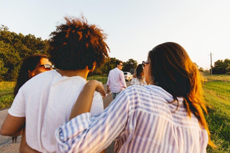 Vista traseira homem novo de cabelo escuro encaracolado que abraça duas meninas Falam e andam ao longo da estrada imagem de stock