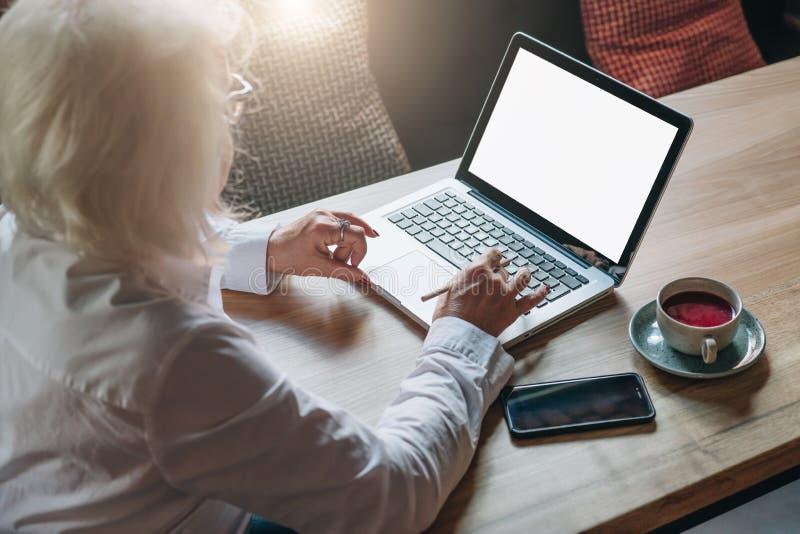 Vista traseira A mulher de negócios aposentou-se o assento no café na tabela, trabalhando no portátil Teletrabalho, educação em l fotos de stock royalty free