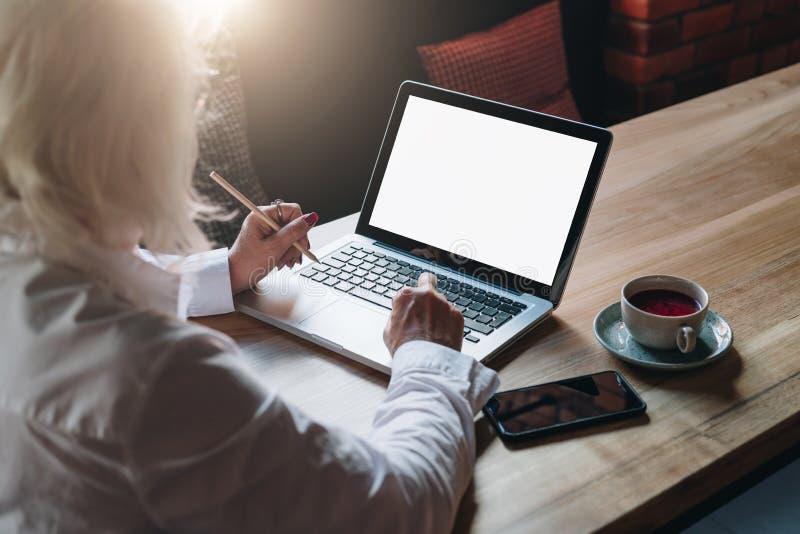 Vista traseira A mulher de negócios aposentou-se o assento no café na tabela, trabalhando no portátil Teletrabalho, educação em l fotografia de stock royalty free
