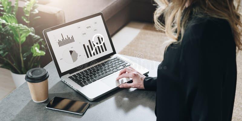 Vista traseira A mulher de negócios nova está sentando-se na tabela, trabalhando no portátil com gráficos, cartas, diagramas, pro imagem de stock
