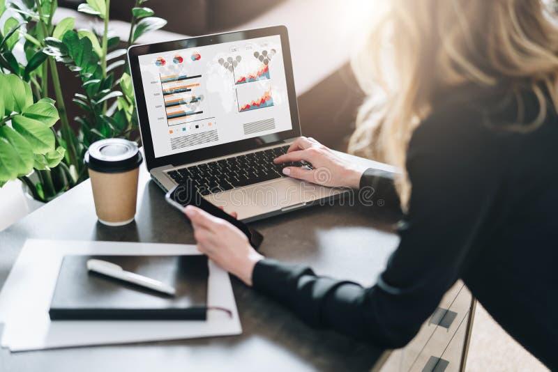Vista traseira A mulher de negócios nova está trabalhando no portátil com gráficos, cartas, diagramas, programações na tela Merca imagens de stock royalty free