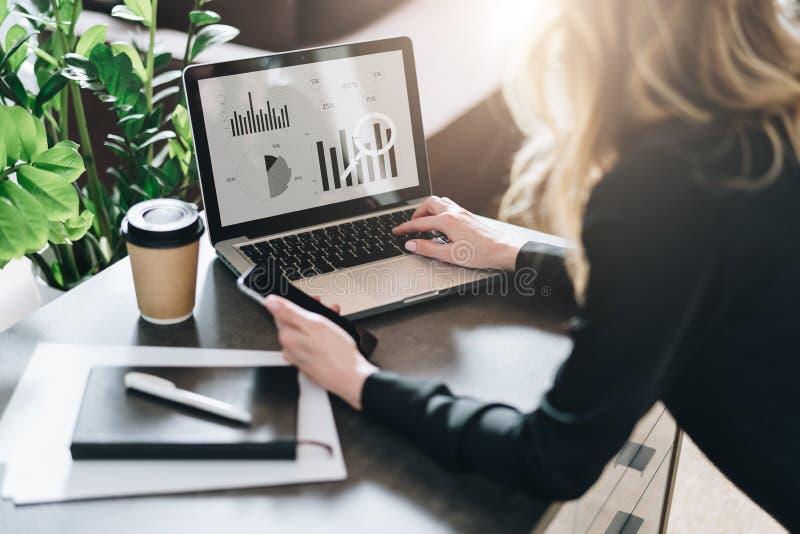 Vista traseira A mulher de negócios nova está trabalhando no portátil com gráficos, cartas, diagramas, programações na tela Merca fotos de stock