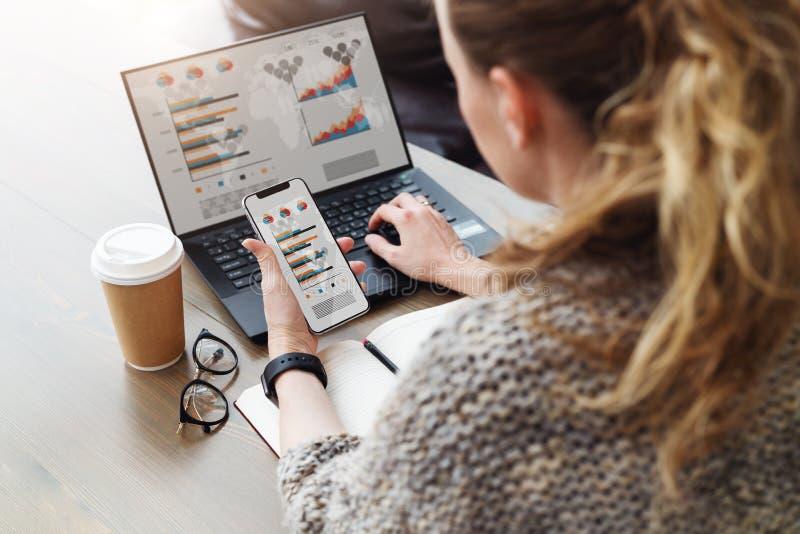 Vista traseira Mulher de negócios nova que senta-se no escritório que trabalha no laptop com gráficos, cartas, diagramas no monit imagem de stock