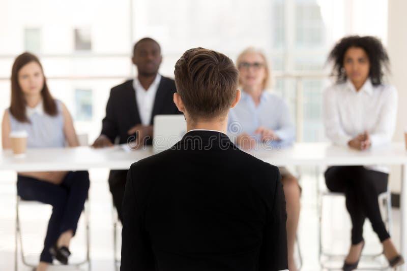 Vista traseira no candidato a emprego durante a entrevista com equipe da hora fotografia de stock royalty free
