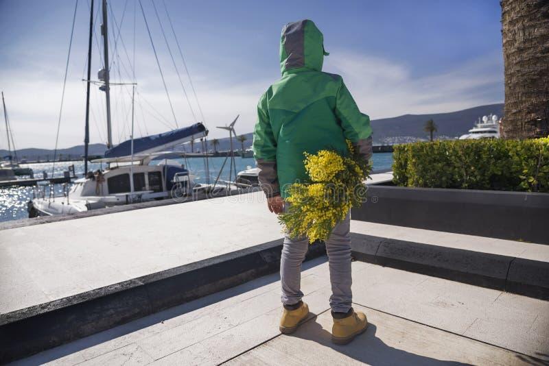 Vista traseira no menino da criança em Porto Montenegro, Montenegro, Tivat, dia ensolarado da mola que guarda as flores atrás da  imagens de stock