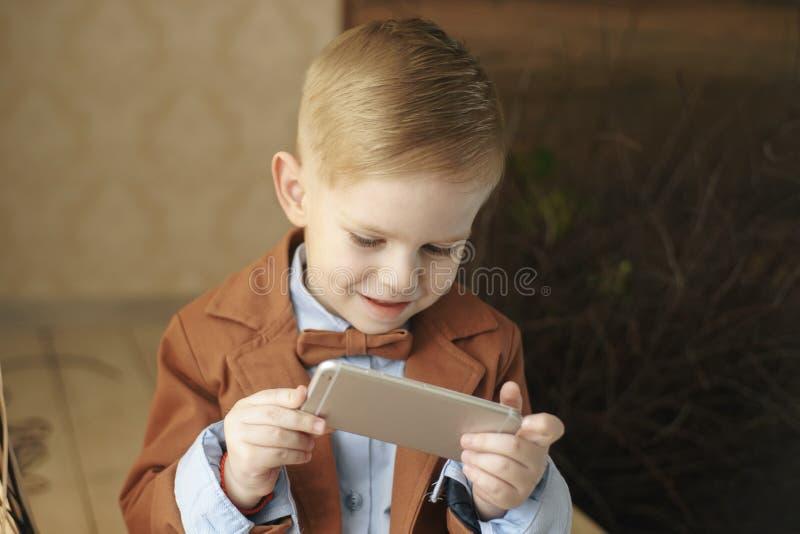 Vista traseira O adolescente, vestido no t-shirt branco, senta exterior no skate e usa o smartphone, dispositivo digital, jogos fotografia de stock