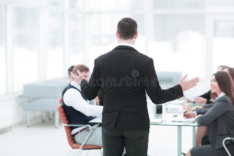 Vista traseira o homem de negócios guarda uma instrução com a equipe do negócio foto de stock