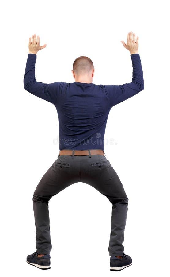 Vista traseira o homem protege as mãos do que está caindo de cima foto de stock royalty free