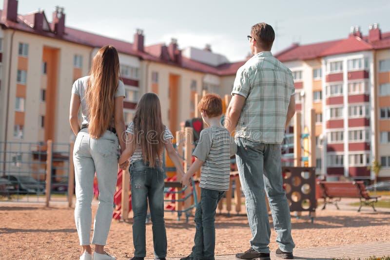 Vista traseira uma família nova está olhando um prédio de apartamentos novo imagem de stock