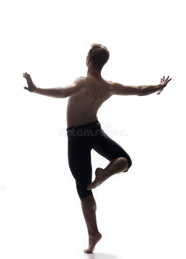A vista traseira, uma parte traseira do homem novo, dançarino de bailado, levantando arma estendido, posição em um pé no ar, fotos de stock