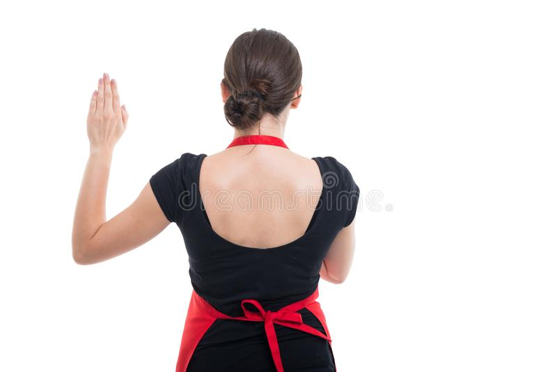 Vista trasera de la mano de levantamiento del vendedor de la muchacha para arriba fotografía de archivo libre de regalías