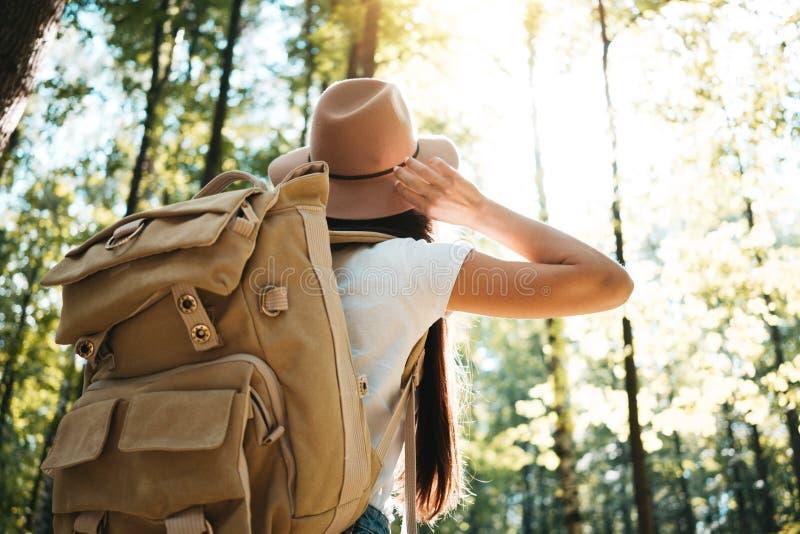Vista trasera de la mochila del viajero del primer y del sombrero que lleva de la muchacha del inconformista Los jóvenes hacen fr fotografía de archivo
