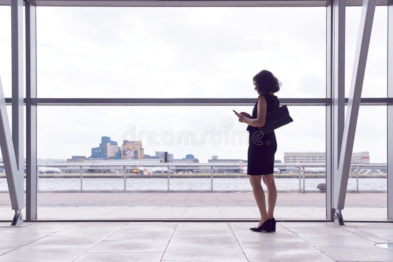 Vista Trasera De La Mujer Empresaria Usando El Teléfono Móvil Parado Por Una Ventana En El Salón De Salida Del Aeropuerto imagenes de archivo