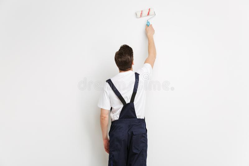 Vista trasera de la pared joven de la pintura del constructor con el rollo de la pintura imagenes de archivo