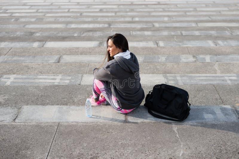 Vista trasera de la sentada urbana femenina del atleta imagen de archivo libre de regalías