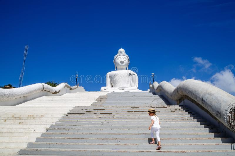 Vista trasera de la situación de la niña cerca de la estatua grande de Buda en Phuket, Tailandia Concepto de turismo en Asia y fa fotografía de archivo