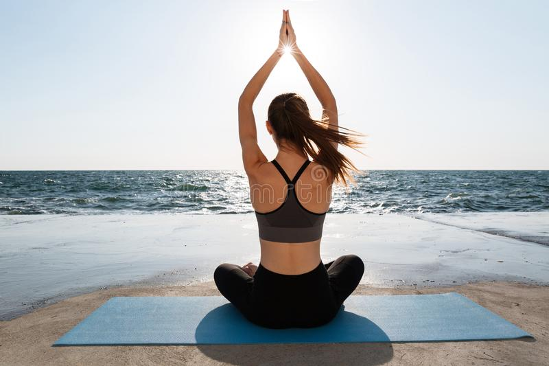 Vista trasera de la yoga practicante de la muchacha atractiva joven que se sienta en el PA imagen de archivo libre de regalías
